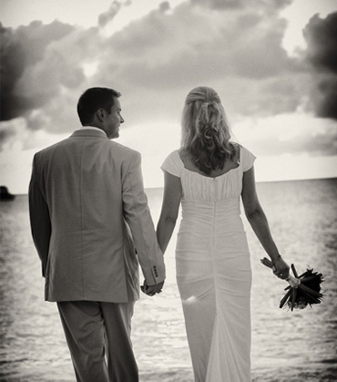 Sepia tone photograph of a Bride and Groom walking on the Beach